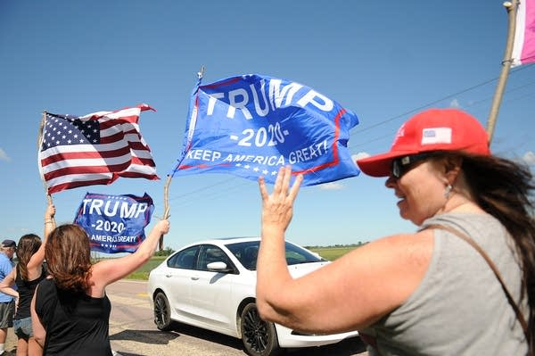 """A Trump supporter holds up four fingers, chanting """"Four More Years."""""""