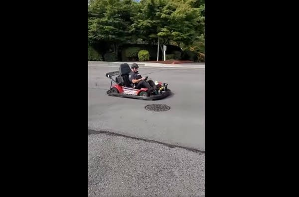 A police officer driving a go-kart down a wide, residential street