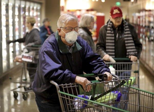 A man shops at a supermarket, wearing a mask.