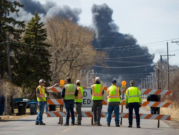 A group of onlookers watch a plume of black smoke billow.