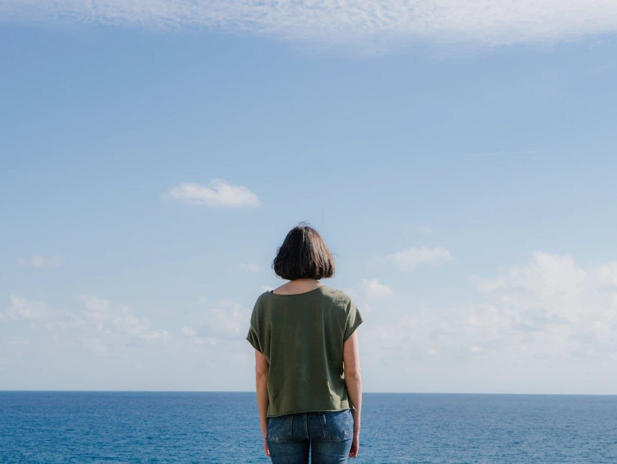 A woman faces the horizon.
