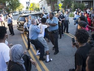 Officers struggle with a demonstrator.