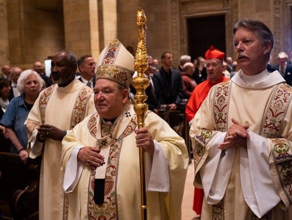 Men in robes holding a staff walk down a church aisle.