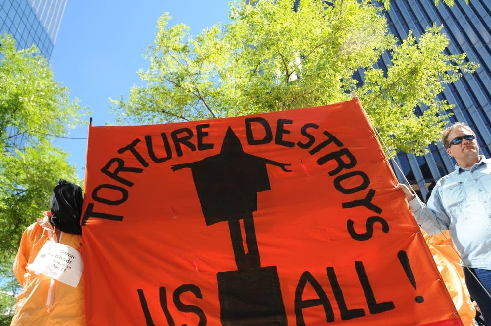 Protesters hold a sign in opposition of torture
