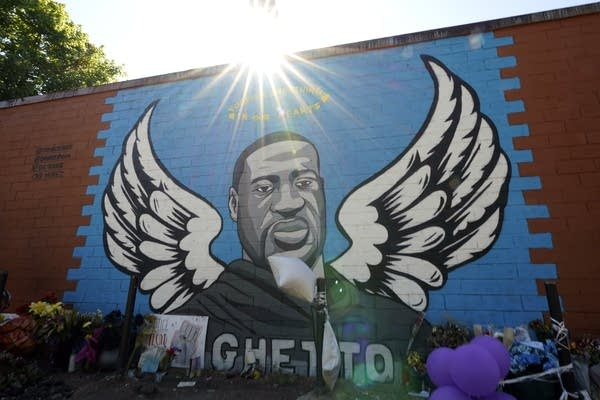 The sun shines above a mural honoring George Floyd.