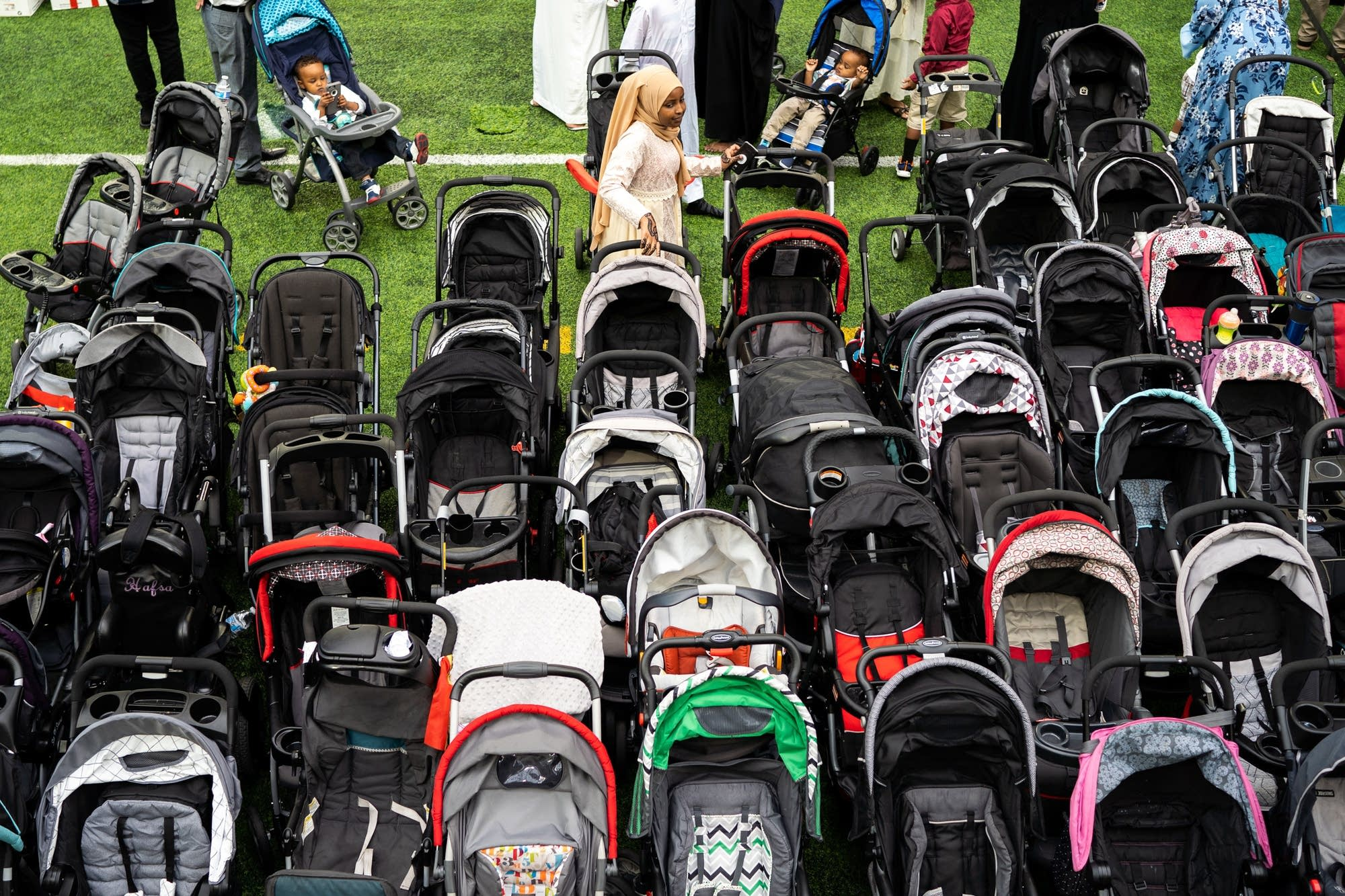 Strollers stack up as people find their spots for morning prayer.