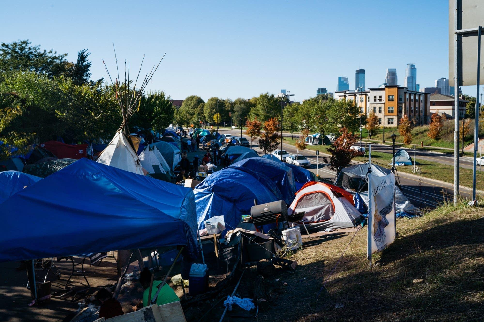 Tents fill a strip of land near Hiawatha Ave.