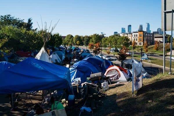 Tents fill a strip of land near Hiawatha Ave.