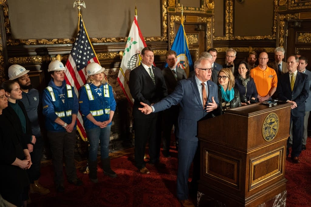 Gov. Walz gestures to renewable energy workers during a press conference