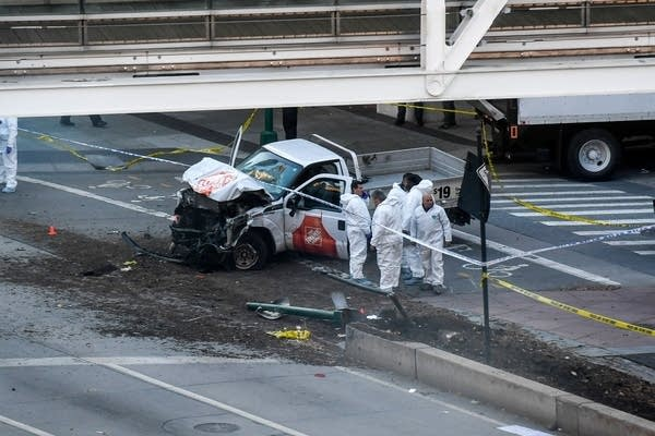 Investigators inspect a truck following a shooting incident in New York