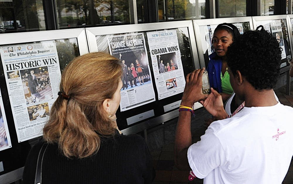 Students take photos of front pages at the Newseum