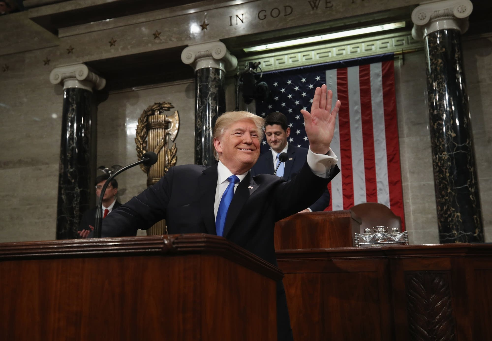 Donald Trump waves as he arrives during the State of the Union address