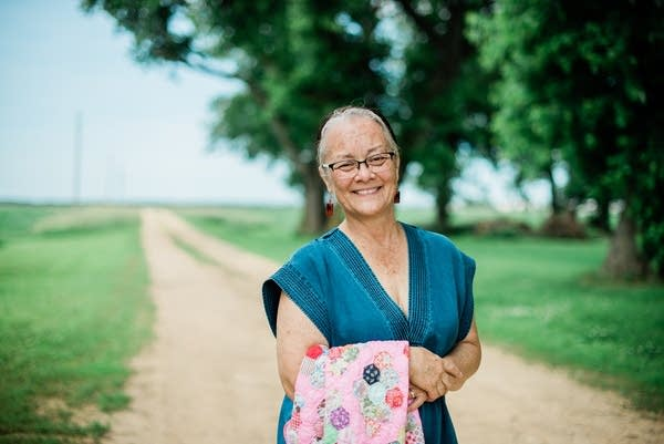 woman standing on gravel road holding quilt
