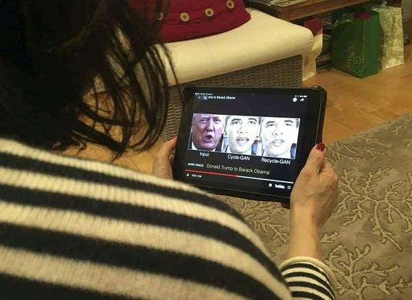 A woman watches a video on a small tablet.