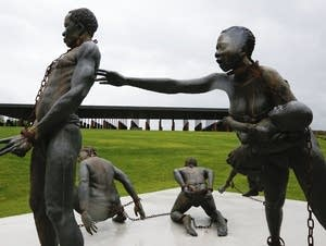 A statue depicting chained people is on display at the memorial.