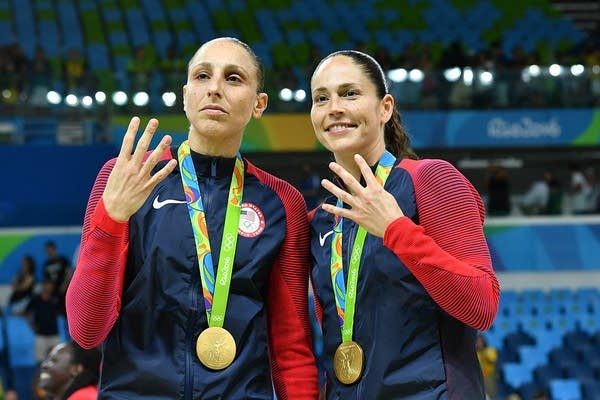 Two women hold up four fingers while wearing gold medals.