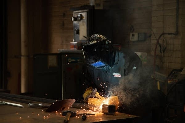 Sparks fly as Nick Bounds wears a welding mask and cuts a new key.