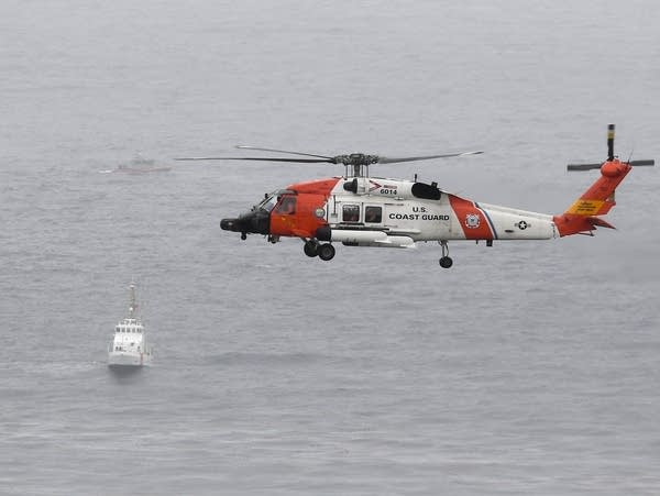 A U.S. Coast Guard helicopter flies over boats