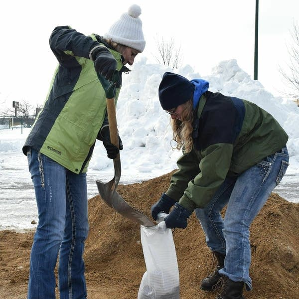 Elaine Hardee, left, scoops sand into a bag held by Meagan Hardee