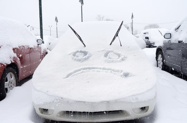 Car covered in snow with a sad frowny face carved into snow on hood