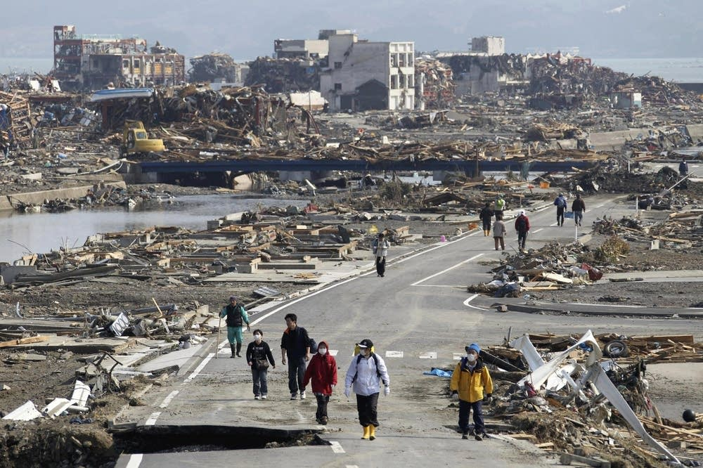 People walk the damaged streets