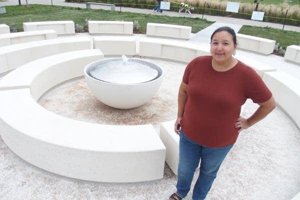 A woman stands near a circular sculpture.