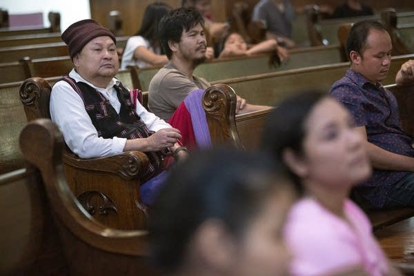 People, including a man in traditional Karen clothing, sit in pews.