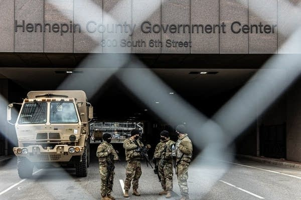 National Guard troops stand outside a building.