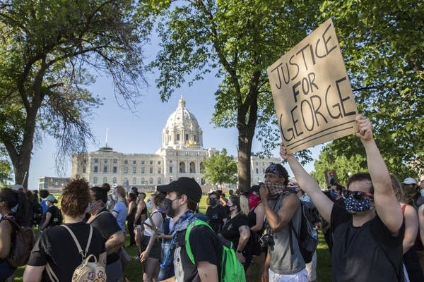 Protesters march by the Minnesota State Capitol building.