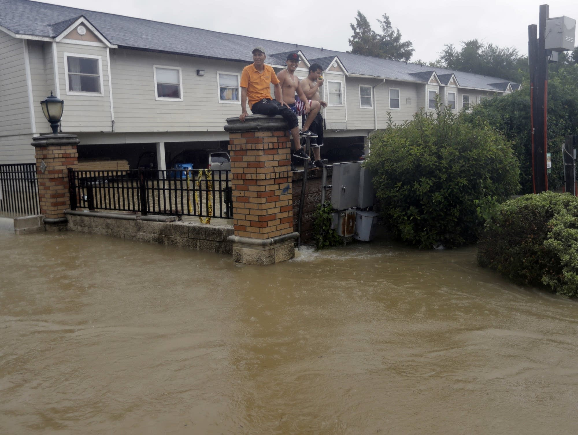 Residents sit on a fence surrounded by floodwaters
