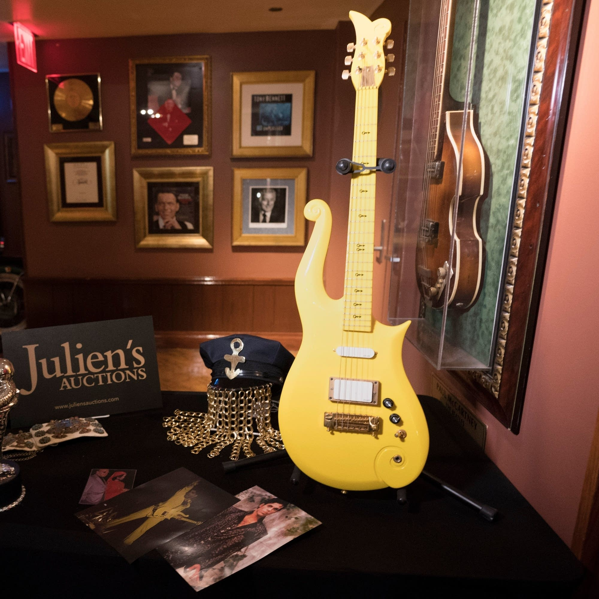 Prince's yellow Cloud guitar displayed along with other auction items.