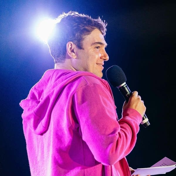 Man in pink hooded sweatshirt standing on a stage and holding a microphone