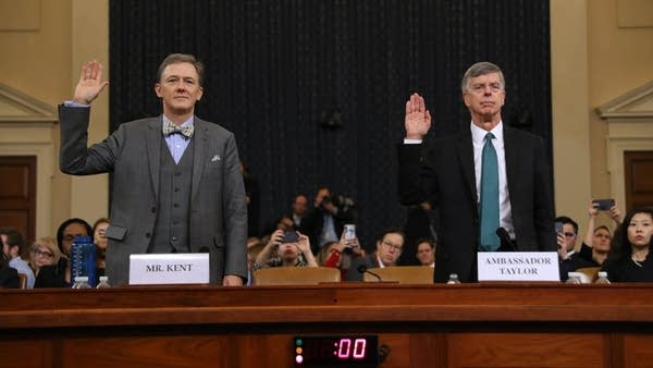 Two men are sworn in before a public hearing.