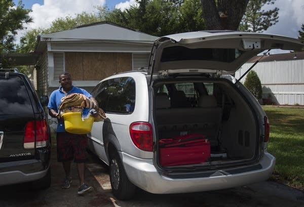 Roberto Guzman carries belongings from his mobile home as he evacuates.