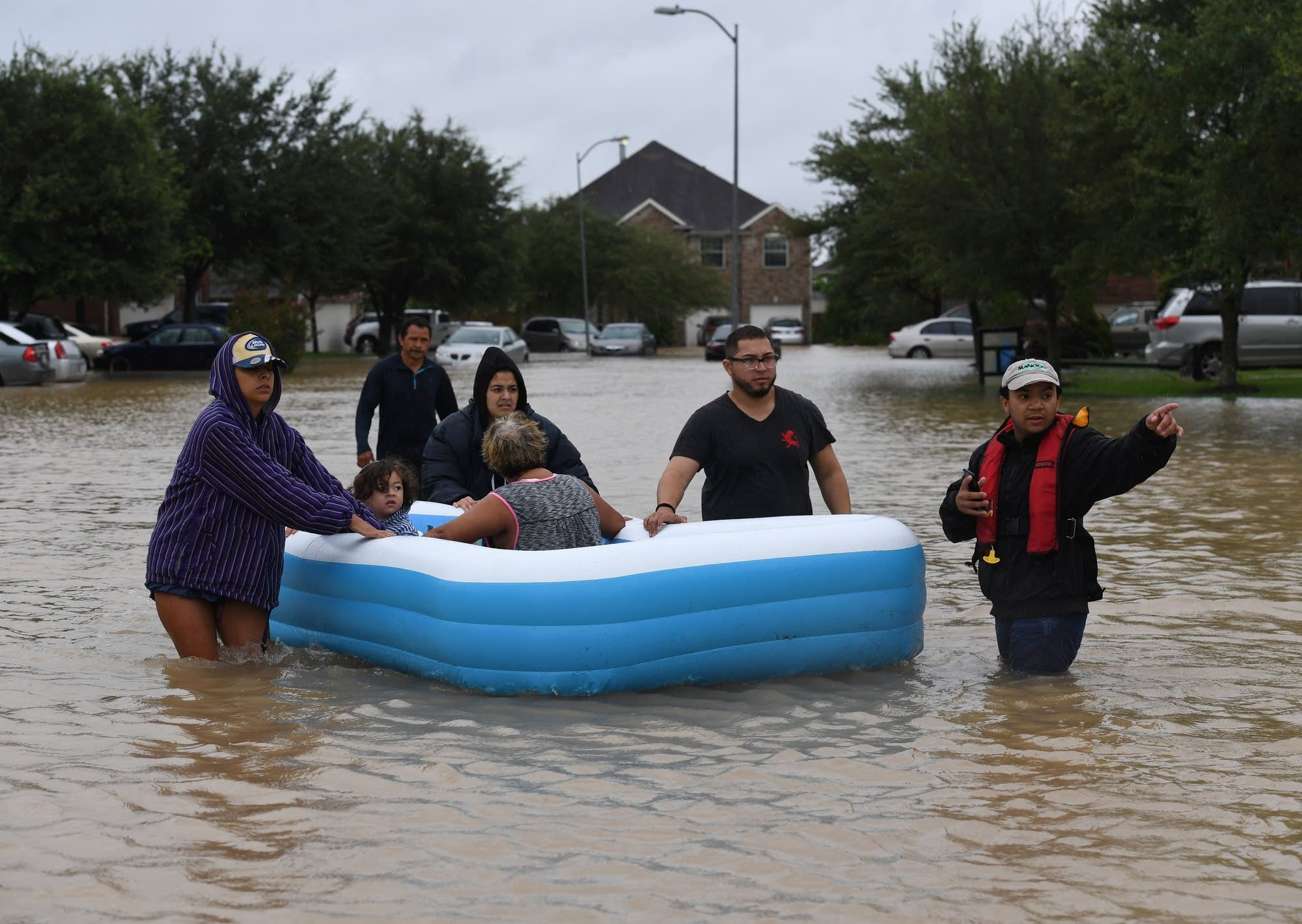 Billy Argueta, right, helps evacuate a family from their flooded street.
