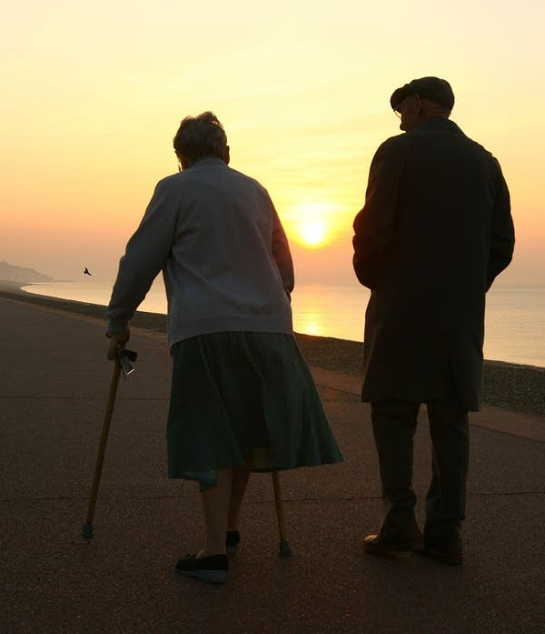 An elderly couple stroll on the sea front.