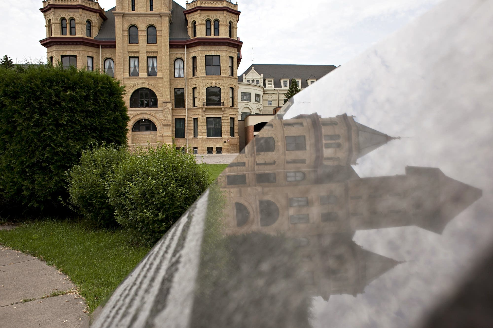 The hospital buildings are reflected in a stone monument in a garden.