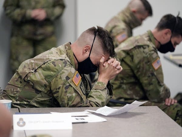 A man wearing military camo and a face mask folds his hands in prayer.