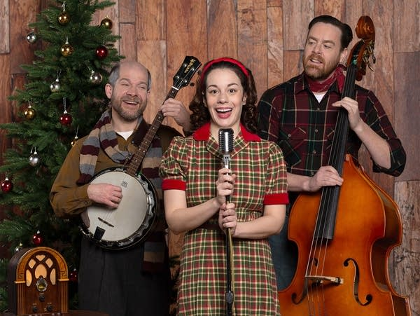 bluegrass band trio on banjo, bass and vocals in front of Christmas tree