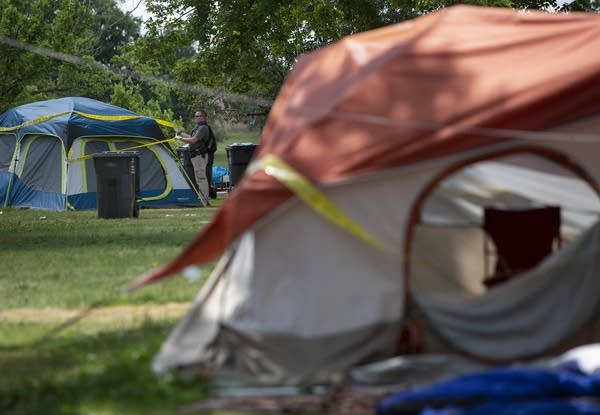 A person ties police tape around a tent.