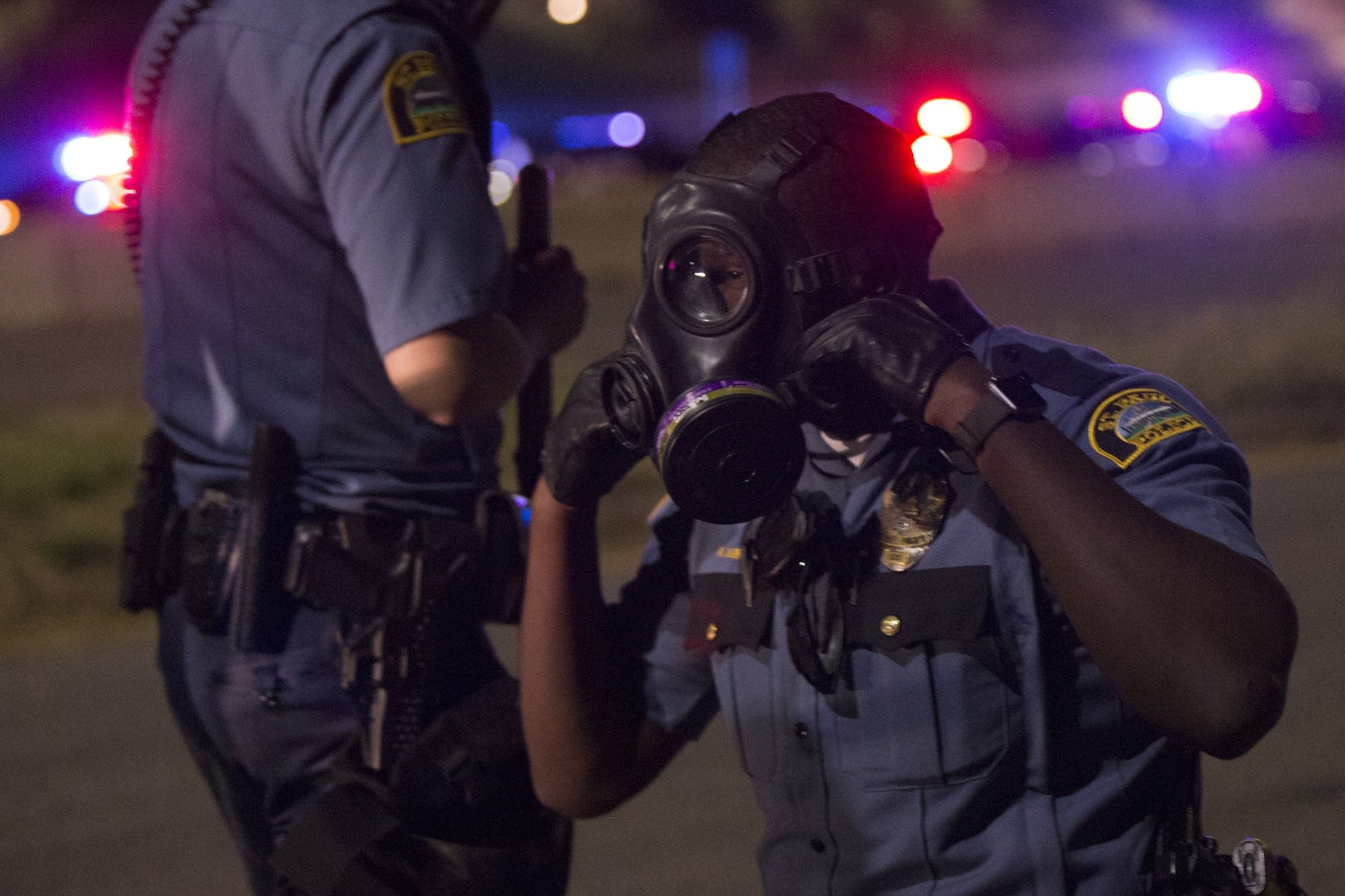 A St. Paul police officer puts on his gas mask.