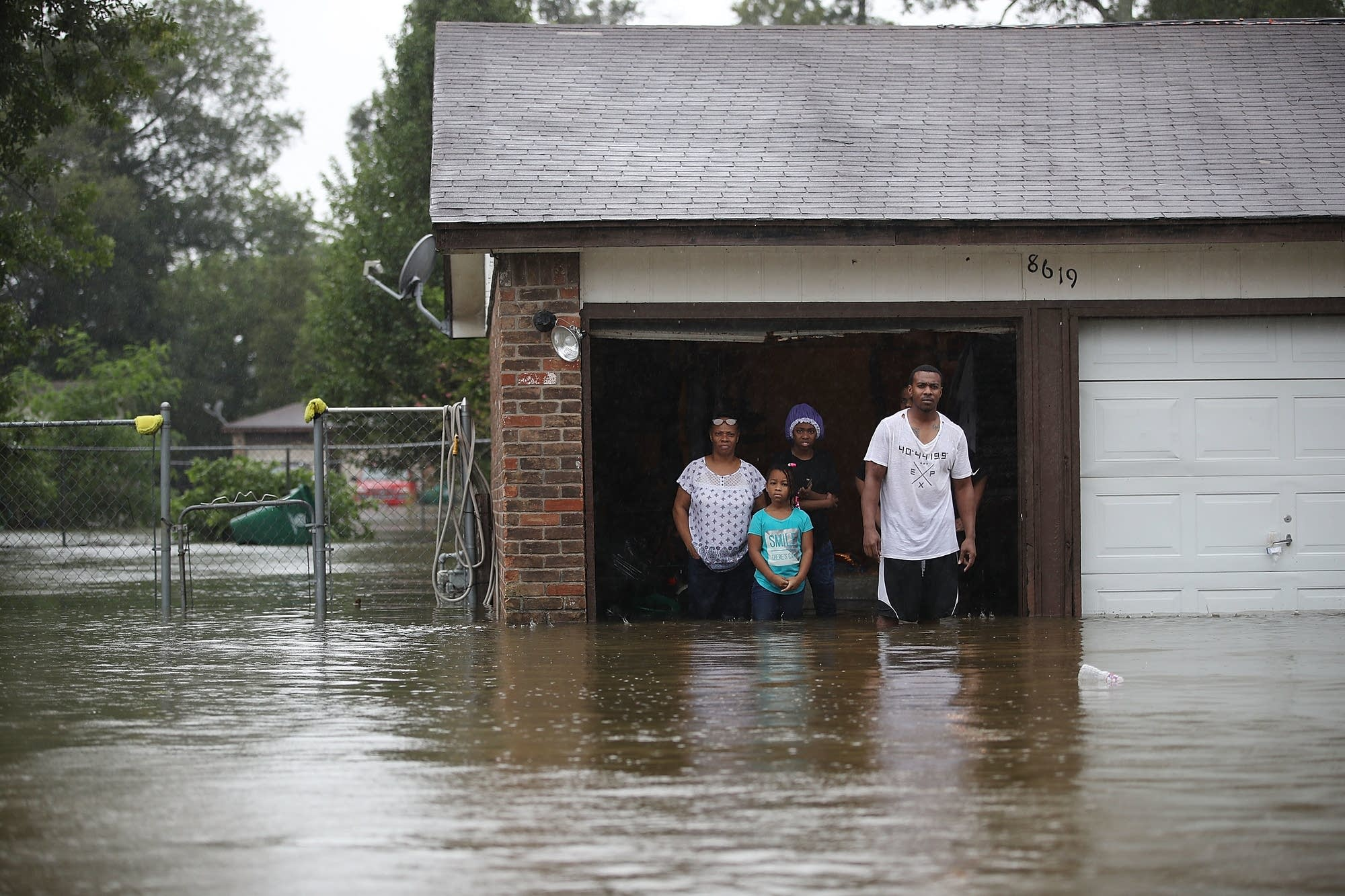 People wait to be rescued from their  flooded homes.