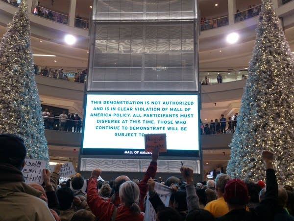 MOA officials flashed a sign at protesters.