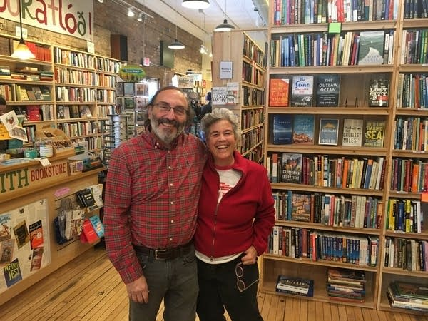 A couple pose for a photo in a bookstore.
