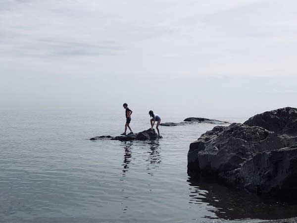 Two kids climbing on rocks in the water.