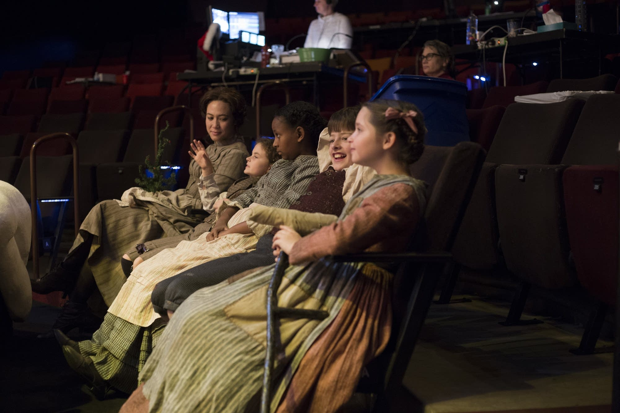Cast members of 'A Christmas Carol' hang out off stage in between scenes.