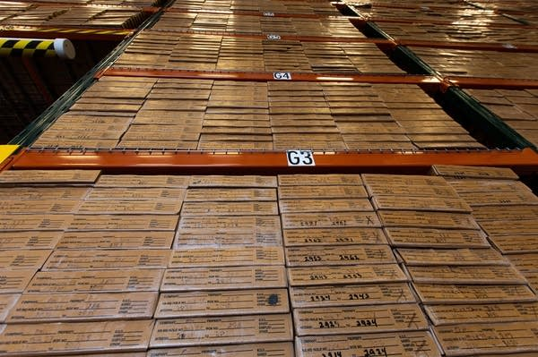 Cardboard boxes and boxes of core samples are stacked a shelf.