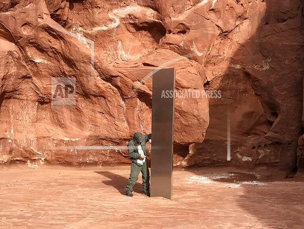 A Utah state worker stands next to a metal monolith in the ground