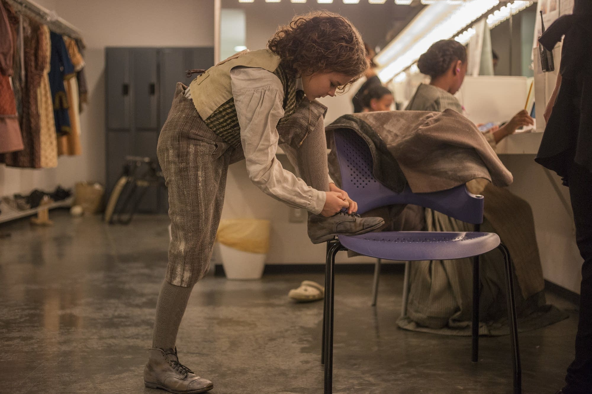 Sophie Jones ties the shoe of her costume before heading to makeup.