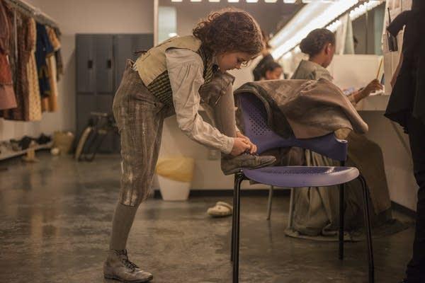 Sophie Jones ties the shoe of her costume before heading to makeup.